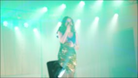 Singer girl brunette sings blurred concert night beautiful light with microphone. slow motion video. Singer in stock video footage