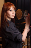 Singer girl in studio. Royalty Free Stock Photo