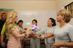 Singer Gloria Trevi receives flowers from inmates. Gloria surrounded by 4 woman inmates is receiving handcrafted flowers inside a prison workshop Stock Photo