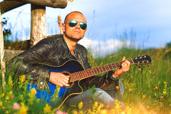 Singer with guitar plays alone in a meadow in nature.  Stock Photo