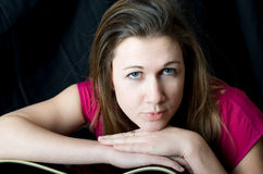 Singer Guitarist Songwriter Portrait. A musician woman looks into a camera in front of a black background leaning on a guitar Stock Photo