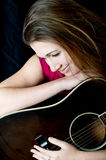 Singer Guitarist Songwriter Woman. A musician woman looks down in front of a black background cradling a guitar Stock Photos