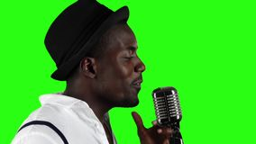 Singer in half of the turnover gesticulating sings into a retro microphone and dancing near it. Green screen. Slow stock video