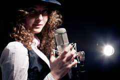 Singer in hat with microphone on the black Stock Photo
