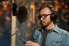 Singer with headphones at music recording studio. Music, show business, people and technology concept - male singer with headphones, microphone and smartphone at Royalty Free Stock Photos