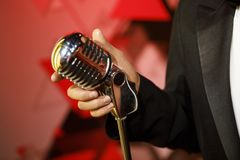 Singer Holding classic microphone. Singer holding retro style microphone stock photography