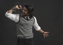 Singer holding a mike and singing Stock Image