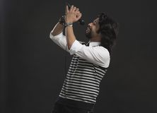 Singer holding a mike and singing Stock Photos