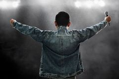 Singer holding wireless microphone on stage royalty free stock photo