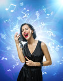 Singer keeping mike against blue music background with notes. Half-length portrait of female musician wearing black evening dress and keeping mike on blue music Royalty Free Stock Photo