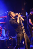 A singer is leaning back while singing a song. Svyatoslav Vakarchuk is leaning back with micro while singing a song at a concert in Helsinki Stock Image