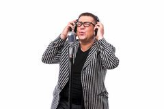 Singer listening music and sing in microphone on white background Royalty Free Stock Photo