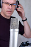 Singer the man. The singer the man in headphones before a microphone stock photography