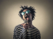 A singer. A man is wearing sunglasses and singing with a microphone in his head Stock Photo