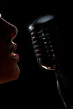 Singer with microphone. Singer in front of a microphone. Isolated on a black background Royalty Free Stock Photography
