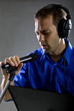 Singer with a Microphone. Male voice over artist or singer on a microphone wearing a blue shirt on a concrete background Royalty Free Stock Photography