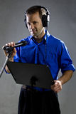 Singer with a Microphone. Male voice over artist or singer on a microphone wearing a blue shirt on a concrete background Stock Photo