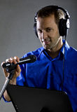 Singer with a Microphone. Male voice over artist or singer on a microphone wearing a blue shirt on a concrete background Royalty Free Stock Images