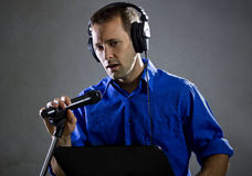 Singer with a Microphone. Male voice over artist or singer on a microphone wearing a blue shirt on a concrete background Stock Photos