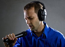 Singer with a Microphone. Male voice over artist or singer on a microphone wearing a blue shirt on a concrete background Royalty Free Stock Photo