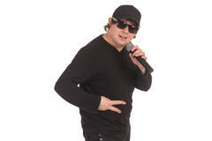 Singer with the microphone. Man is singing with the microphone in the dark glasses and black cap Royalty Free Stock Photo