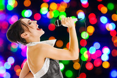 Singer at a night club. Singer artist performance at a night club against colored lights wall Royalty Free Stock Photos