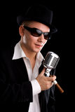 Singer with old fashioned mic. And black hat Royalty Free Stock Photography
