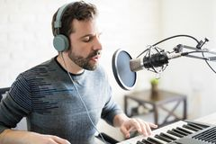Singer in a online radio show. Good looking latin man singer with headphones singing a song and playing piano into mic at radio station Stock Photos
