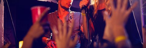 Singer performing with guitarist on stage. In nightclub Royalty Free Stock Image