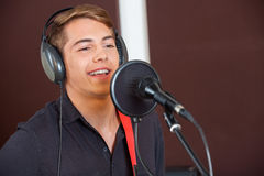 Singer Performing While Looking Away In Studio. Handsome male singer performing while looking away in recording studio Stock Photos