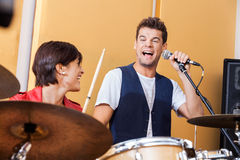 Singer Performing While Looking At Drummer. Happy male singer performing while looking at female drummer in studio Stock Photography