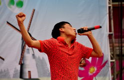 Pengzhou, China: Singer Performing on Outdoor Stage. Singer performing on an outdoor stage hits an emotional moment in his song at the Venus Wedding Plaza Spring stock images