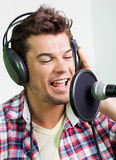 Singer Performing In Recording Studio. Closeup of male singer performing in recording studio Stock Image