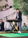 Singer performs a song, accompanying himself on a keyboard instr Stock Photo