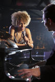 Singer And Pianist On Stage. Happy female jazz singer and pianist on stage Royalty Free Stock Photography