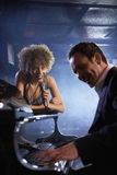 Singer And Pianist On Stage. Happy female jazz singer and pianist on stage Stock Images