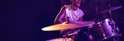 Singer playing drums while performing in nightclub. Male singer playing drums while performing in nightclub Stock Photo