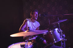 Singer playing drums while performing in nightclub. Male singer playing drums while performing in nightclub Stock Photos