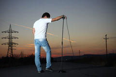 Singer portrait. Lead vocalist posing in the middle of the road at sunset stock photo