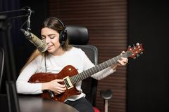 Singer in a radio show. Young female singer playing guitar and singing in microphone at radio station stock photo