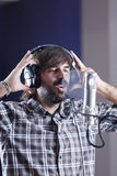 Singer in a recording room. Male singer with headphones is rehearsing in a recording room at a recording studio - focus on face Stock Photos