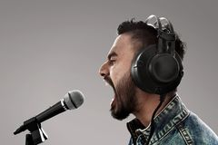 Singer recording a song on gray background stock photography