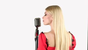 Singer in a red dress is singing into a retro microphone. White background. Back view. Singer in a red dress in a spacious studio sings in a retro microphone a stock video
