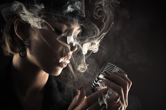 Singer with retro microphone and cigarette smoke Royalty Free Stock Images