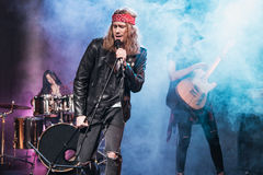 Singer with rock and roll band performing music on stage Royalty Free Stock Images