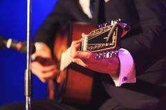 Singer playing at guitar pop or classic music on a colorful fancy background. Man in elegant costume playing a guitar during of the concert. Hands playing stock photos