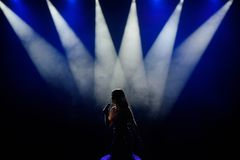 Singer in silhouette. A young woman singer on stage during a concert. stock images