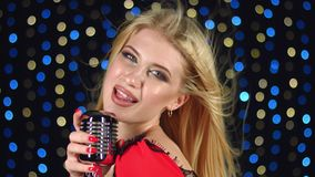 Singer sings into the microphone. Singer sings in a retro microphone, in the background the colorful lights stock footage