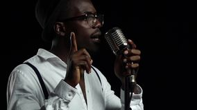 Singer sings into a retro microphone and dancing near it. Black background. Slow motion. Close up stock footage