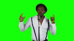 Singer sings into a retro microphone spinning and dancing around him. Green screen. Singer sings into a retro microphone spinning and dancing around him in a stock video footage